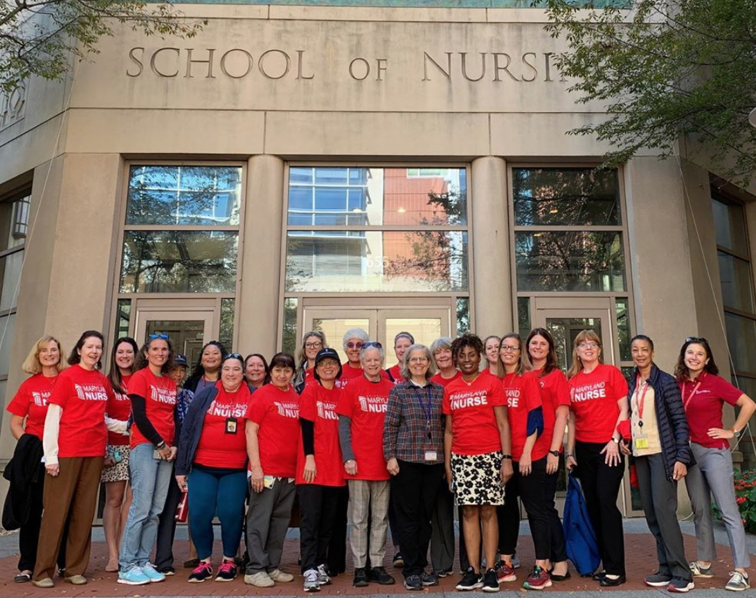 UMSON faculty and staff wearing red in front of the building