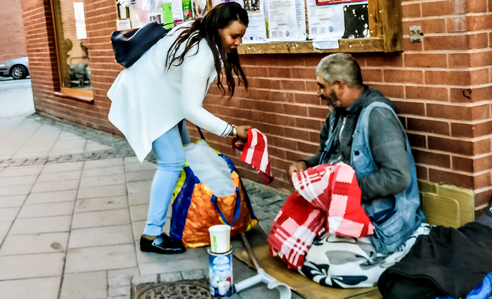 A woman hands a piece of clothing to a man experiencing homelessness.