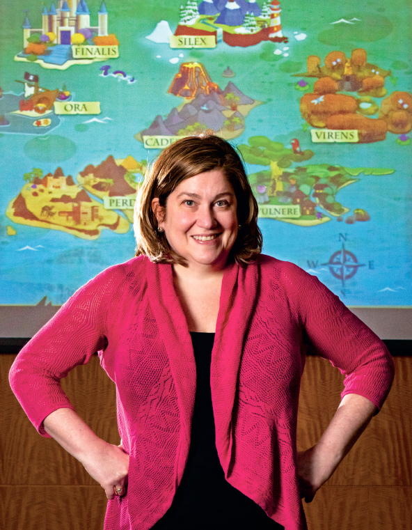 Stacy Brull stands in front of a screen showing the game she developed