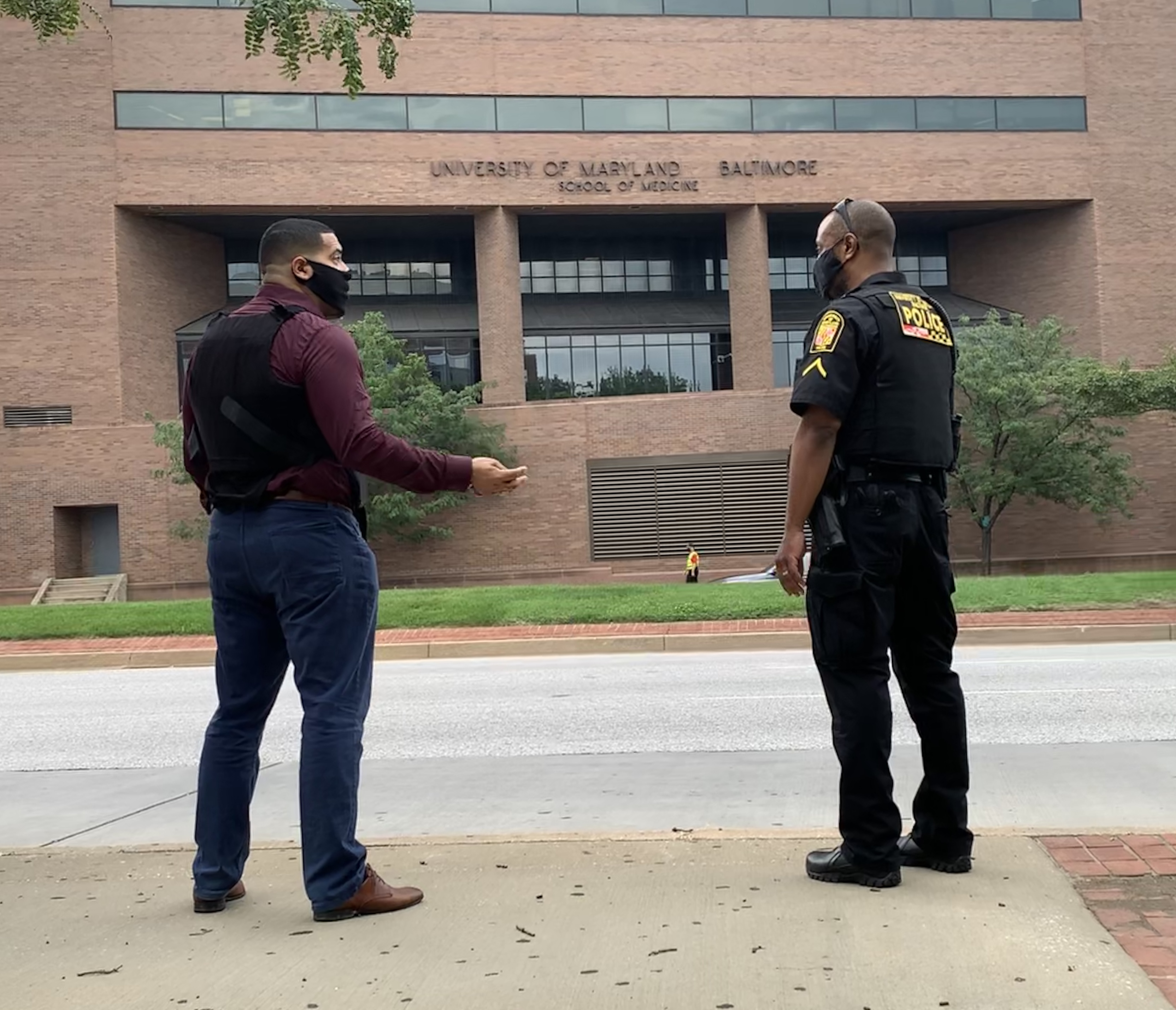 Jonathan Alfaro and Pfc. Yale Partlow stand socially distanced wearing masks, facing each other and talking. The University of Maryland, Baltimore School of Medicine building is shown behind them.